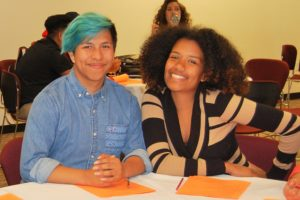 Two students sitting and smiling at the camera