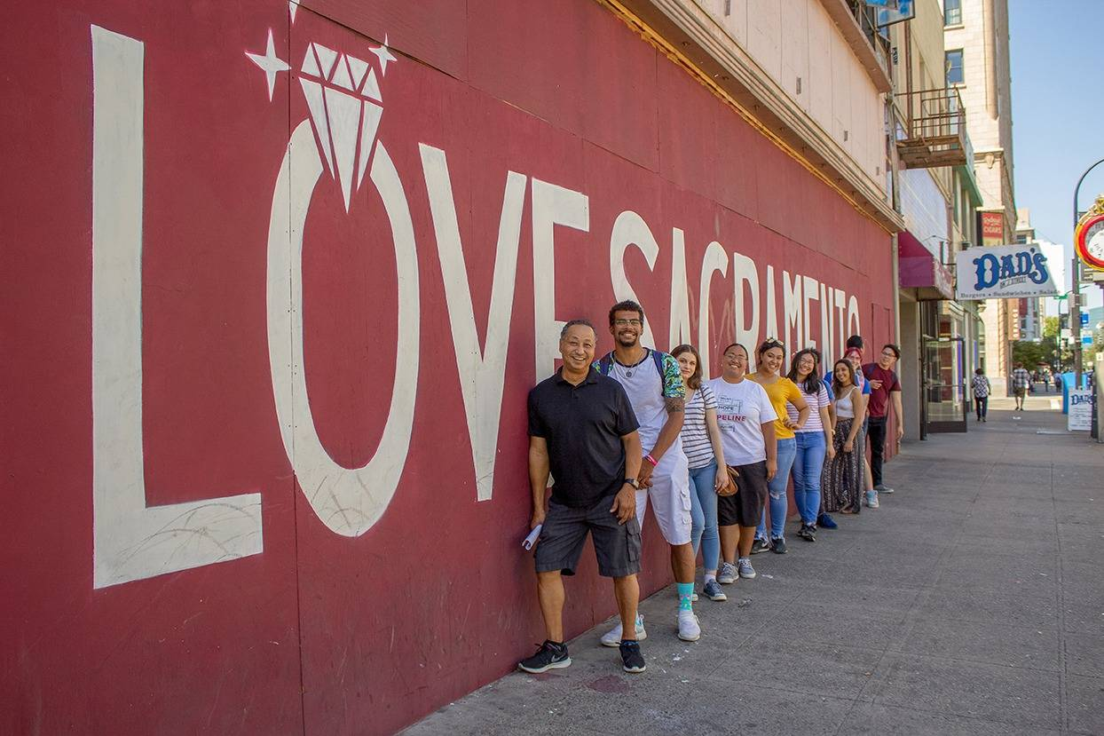 DLA Peer Mentors next to a mural that says, 'Love Sacramento'.